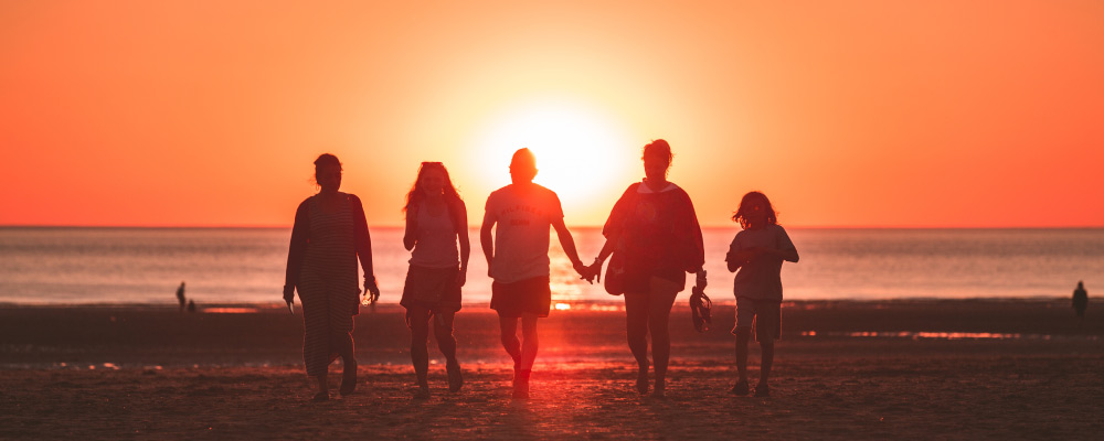 family of five walking on the beach at sunset